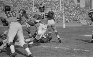 09 Nov 1955, Los Angeles, California, USA --- Original caption: Los Angeles Rams' Tank Younger, (35), swivels around left end for a 19 yard gain against the San Francisco 49ers during the game in Los Angeles on November 6th. He was finally stopped by the 49ers' Dicky Moegle, (C, partly hidden), as Moegle slips through a partial block by Tom Fears, (80), a Ram end. The Rams won 27-14. --- Image by © Bettmann/CORBIS