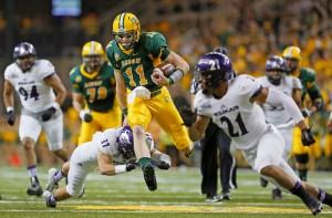 North Dakota State quarterback Carson Wentz leaps Weber State defender Mitch Tulane on a 27 yard touchdown run Saturday, Sept. 12, 2015, at the Fargodome. David Samson / The Forum
