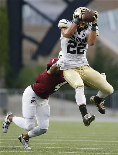 Colorado wide receiver Nelson Spruce (22) makes the reception in front of Massachusetts defensive back Randall Jette (4) in the fourth quarter of an NCAA college football game in Foxborough, Mass., Saturday, Sept. 6, 2014. Colorado won 41-38. (AP Photo/Michael Dwyer)